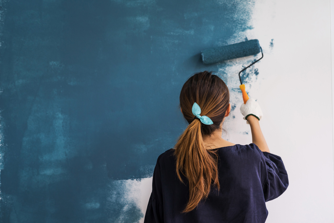 Image of a female painter applying a blue coat of a paint to a white wall with a roller.